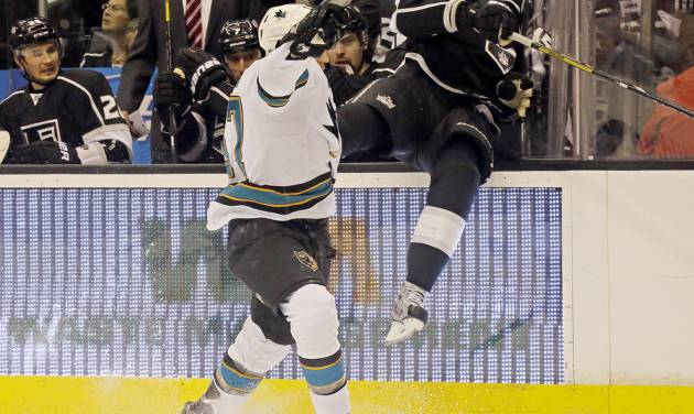 San Jose Sharks center Tommy Wingels (57) checks Los Angeles Kings defenseman Keaton Ellerby (5) into the bench in the first period of an NHL hockey game in Los Angeles Saturday, April 27, 2013. (AP Photo/Reed Saxon)
