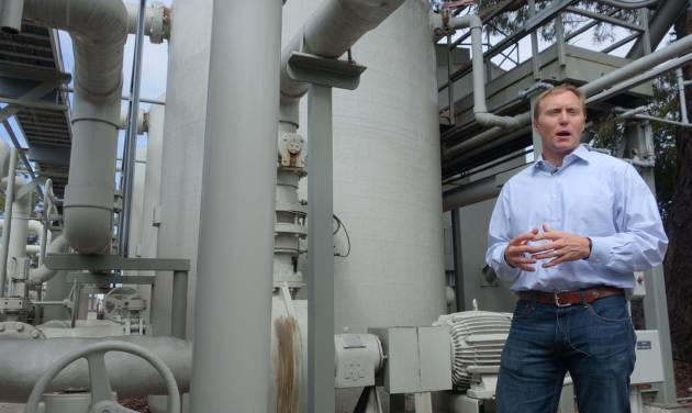 In this April 25, 2014 photo, Joshua Haggmark, interim resources manager for Santa Barbara, Calif., stands next to a desalination plant, which removes salt from ocean water, in Santa Barbara, Calif.  The city is considering restarting the plant as California withers in a drought. (AP Photo/Alicia Chang)
