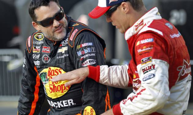 Tony Stewart, left, talks with Kevin Harvick before qualifying for Sunday's NASCAR Sprint Cup series auto race at Charlotte Motor Speedway in Concord, N.C., Thursday, May 22, 2014. (AP Photo/Terry Renna)