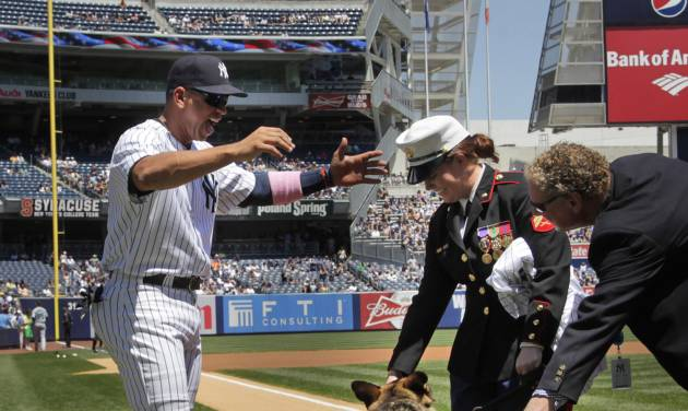New York Yankees' Alex Rodriguez, left, keeps his distance from combat dog Sgt. Rex while greeting former Marine Cpl. and Purple Heart recipient Megan Leavey, center, as Yankees team president Randy Levine, right, looks on during a ceremony before the start of a baseball game against the Seattle Mariners at Yankee Stadium in New York, Sunday, May 13, 2012. Through two tours of duty in Iraq, Sgt. Rex was by Leavey's side. (AP Photo/Seth Wenig)