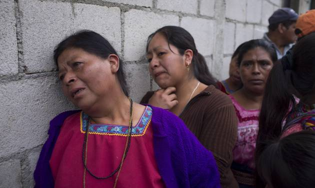 Relatives of victims react as police take away the bodies, not seen, after an attack in San Jose Nacahuil, on the outskirts of Guatemala City, Sunday, Sept. 8, 2013. Men firing from a car poured gunshots into three cantinas in this rural town, killing at least 10 people and injuring 19, local firefighters said Sunday. (AP Photo/Moises Castillo)