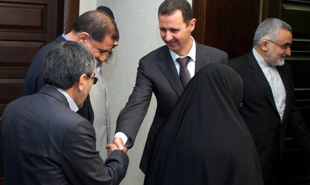 In this photo released by the Syrian official news agency SANA, Syrian President Bahsar Assad, center, shakes hands with one of the Iran's parliamentary committee on national interest and foreign policy, in Damascus, Syria, Monday, April 22, 2013. Assad said during the meeting that the Middle East is being subjected to plans that targets its stability and unity of its territories. (AP Photo/SANA)