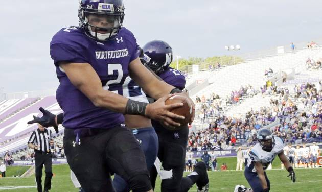 "FILE - In this Sept. 21, 2013 file photo, Northwestern quarterback Kain Colter (2), wears APU for ""All Players United"" on wrist tape as he scores a touchdown during an NCAA college football game against Maine in Evanston, Ill. The decision to allow Northwestern football players to unionize raises an array of questions for college sports. Among them, state schools vs. public schools, powerhouse programs vs. smaller colleges.  (AP Photo/Nam Y. Huh, File)"
