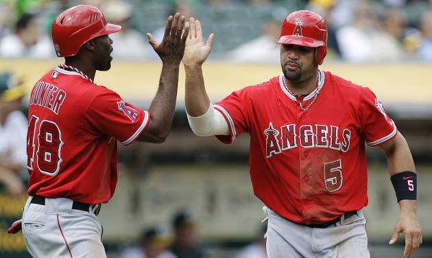 Los Angeles Angels' Torii Hunter, left, and Albert Pujols (5) celebrate after scoring against the Oakland Athletics in the third inning of a baseball game, Wednesday, Sept. 5, 2012, in Oakland, Calif. Both scored on a single by Howie Kendrick. (AP Photo/Ben Margot)