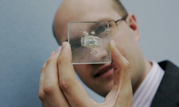 FILE - In this May 23, 2014 file photo, Christie's Head of Travel, Science and Natural History Sale James Hyslop poses for photographs with a 1958 prototype integrated circuit mounted on glass designed by Nobel Prize Physics winner Jack Kilby at Texas Instruments, at premises of the auction house in London, Friday, May 23, 2014.  The prototype microchip, a historical contribution to the modern computing era, is estimated to fetch between $1,000,000 and $2,000,0000 at a June 19 sale in New York.  (AP Photo/Matt Dunham, File)
