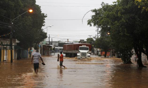 A truck makes it's way down a flooded street after heavy rain storms in Recife, Brazil, Thursday, June 26, 2014. The World Cup soccer match between the USA and Germany will be played at the Arena Pernambuco in Recife today.  (AP Photo/Petr David Josek)
