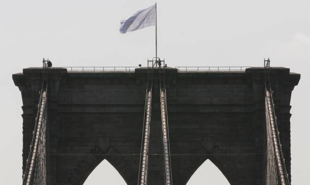 "FILE - In a Tuesday, July 22, 2014 file photo, New York City Police officers stand at the base of a white flag flying atop the west tower of the Brooklyn Bridge after two large American flags atop the Brooklyn Bridge were replaced sometime during the night with white banners. Mayor Bill de Blasio said Monday, July 28, 2014 that last week's security breach at the Brooklyn Bridge is ""a wake-up call, "" and that that the NYPD has increased security on all of New York City's bridges. (AP Photo/Richard Drew, File)"