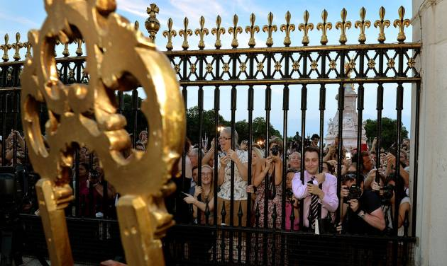 The large waiting crowds cheers as they read the news on an easel in the forecourt of Buckingham Palace, to announce the birth of a baby boy, at 4.24pm to William and Kate, the Duke and Duchess of Cambridge at St Mary's Hospital in west London,   Monday July 22, 2013. The notification was  set up on an easel facing the gates for public view. The child is now third in line to the British throne.  (AP Photo/John Stillwell, Pool)