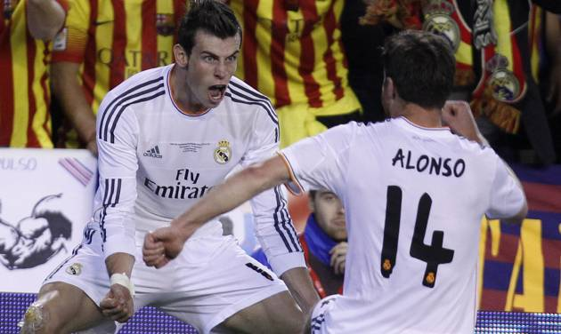 Real's Gareth Bale, left celebrates with Xabi Alonso after scoring his team's 2nd goal during the final of the Copa del Rey between FC Barcelona and Real Madrid at the Mestalla stadium in Valencia, Spain, Wednesday, April 16, 2014. (AP Photo/Alberto Saiz)