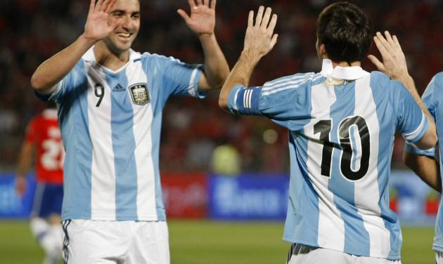 Argentina's Gonzalo Higuain celebrates with Lionel Messi, right, after scoring against Chile during a World Cup 2014 qualifying soccer match in Santiago, Chile, Tuesday, Oct. 16, 2012. (AP Photo/Luis Hidalgo)