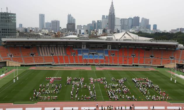 """The volunteers form the words """"Tokyo 2020"""" to promote the 2020 Olympic Games which will be hosted in Tokyo during an event at the National Stadium in Tokyo, Sunday, May 25, 2014. Tokyo's National Stadium, the centerpiece of the 1964 Summer Olympics, hosted its final sporting event on Sunday before it will be demolished to make way for a new 80,000-seat structure that will be the main venue of the 2020 Olympics. (AP Photo/Eugene Hoshiko)"""