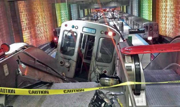 FILE - In this March 24, 2014 file photo, a Chicago Transit Authority train car rests on an escalator at the O'Hare International Airport station after it derailed in Chicago. More than 30 people were injured. A preliminary report released Monday, April 7, 2014, by the National Transportation Safety Board says there wasn't enough distance between an automatic emergency braking mechanism and the end of a train track at Chicago's O'Hare International Airport. (AP Photo/NBC Chicago, Kenneth Webster, File)  MANDATORY CREDIT