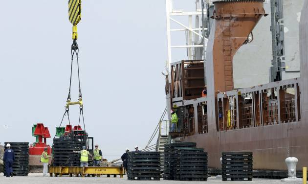 In this Monday, April 21, 2014 photo, workers load materials for export onto the Amsterdam-bound Fortunagracht at the Port of Cleveland in Cleveland. A drop in U.S. exports and lower income from overseas investments drove the U.S. current account deficit to its highest level in 18 months, the Commerce Department reported Wednesday, June 18, 2014. (AP Photo/Tony Dejak)