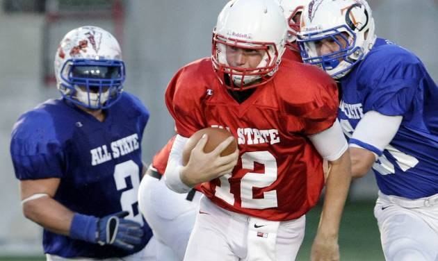 West quarterback Garrett Lorah, center, finds a hole between the East's Hunter Hart and Tyler Clifton during their All State football game at Union High School in Tulsa, Okla., Friday, July 27, 2012. (AP Photo/Tulsa World Michael Wyke) ORG XMIT: OKTUL105