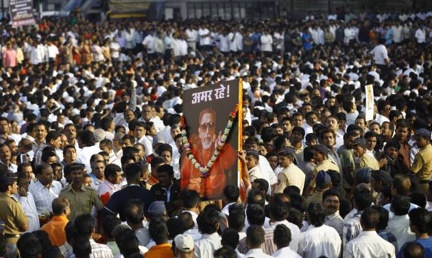 """FILE - In this Nov. 18, 2012 file photo, Indian mourners carry a poster of Hindu hardline Shiv Sena party leader Bal Thackeray with the words """"Long Live"""" during his funeral in Mumbai, India. Indian media say police in Mumbai have arrested two girls who posted a comment on a social networking site criticizing the shutdown of India's financial hub following the death of a Hindu fundamentalist politician over the weekend. (AP Photo/Rafiq Maqbool, File)"""
