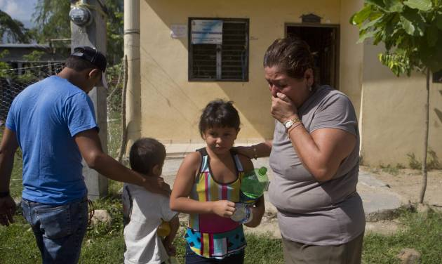 In this Saturday, July 19, 2014 photo, Elsa Lopez, 57, cries as she receives her grandchildren, Sandra, 8, and Cesar, 5, who were deported along with their mother, from the United States a day earlier, in Tocoa, Honduras. Overwhelmed by unaccompanied minors and women with children crossing illegally, U.S. authorities have stepped up deportations back to Central America. (AP Photo/Esteban Felix)