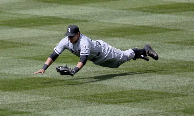 Chicago White Sox Avisail Garcia (26) makes a diving catch on a drive to right by Colorado Rockies DJ LeMahieu during the fourth inning of a baseball game, Wednesday, April 9, 2014, in Denver. (AP Photo/Barry Gutierrez)
