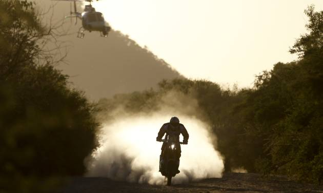 A TV helicopter follows Marc Coma, of Spain, as he rides his KTM motorcycle during the Dakar Rally between the cities of San Miguel de Tucuman and Salta, Argentina, Friday, Jan. 10, 2014. (AP Photo/Victor R. Caivano)