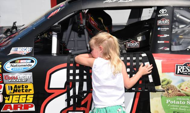 Driver Matt Kenseth's daughter Grace looks inside his car before the NASCAR Nationwide series auto race, Saturday, May 31, 2014, at Dover International Speedway in Dover, Del. (AP Photo/Molly Riley)