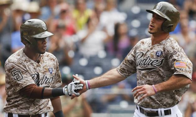 San Diego Padres' Tommy Medica, right, is congratulated by Irving Falu after scoring against the Arizona Diamondbacks on a sacrifice fly by Alexi Amarista during the fourth inning of a baseball game  Sunday, June 29, 2014, in San Diego.  (AP Photo/Lenny Ignelzi)