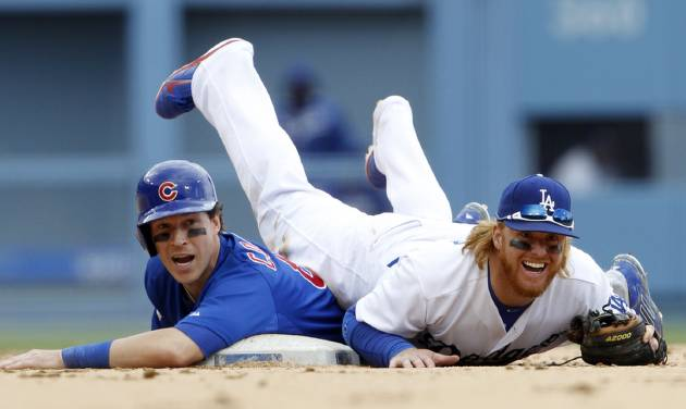 Chicago Cubs' Chris Coghlan, left, and Los Angeles Dodgers second baseman Justin Turner react to the safe call at first on Cubs' Arismendy Alcantara on a double play attempt in the seventh inning of a baseball game on Sunday, Aug. 3, 2014, in Los Angeles. Coghlan was out at second on the play. (AP Photo/Alex Gallardo)
