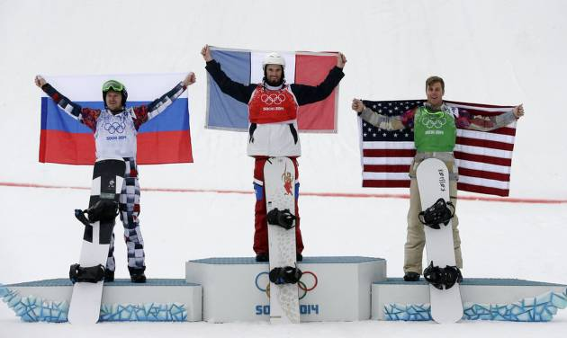 France's Pierre Vaultier, center, celebrates his gold medal with silver medalist Nikolai Olyunin of Russia, left, and bronze medalist Alex Deibold of the United States after the men's snowboard cross final at the Rosa Khutor Extreme Park, at the 2014 Winter Olympics, Tuesday, Feb. 18, 2014, in Krasnaya Polyana, Russia. (AP Photo/Andy Wong)