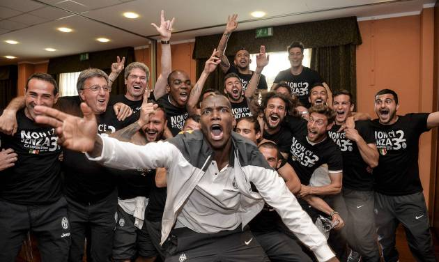 Juventus' Paul Pogba, foreground, celebrate with teammates after winning the Serie A overall soccer title, in a Turin hotel, Italy, Sunday, May 4, 2014. Juventus clinched its third straight and 30th overall Serie A title Sunday without even playing. With second-place Roma losing 4-1 at Catania, Juventus' eight-point lead became insurmountable because Roma only has two matches remaining. Juventus, which has three games to play, can celebrate when it hosts Atalanta on Monday although the Turin squad's players and coach Antonio Conte were already celebrating outside their team hotel wearing championship T-shirts. (AP Photo/Daniele Badolato, Lapresse)