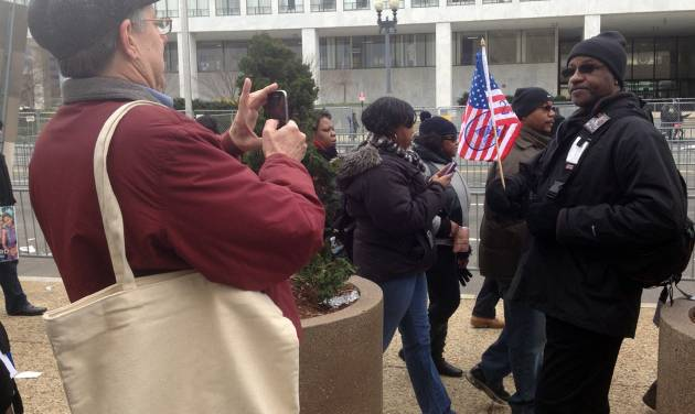 Curator William Pretzer takes a photograph of Larry Holmes, 56, of Washington with his Obama inauguration flag Monday, Jan. 21, 2013, at the inauguration in Washington. Pretzer, a curator from the Smithsonian National Museum of African American History and Culture, was asking for objects to be donated for future exhibitions. The Smithsonian's National Museum of African American History and Culture will open its doors during President Barack Obama's second term with a large display about the first black president. (AP Photo/Brett Zongker)