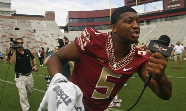 Videographer in tow, Florida State quarterback Jameis Winston (5) searches for teammates to interview during their NCAA college football media day on Sunday, Aug. 10, 2014, in Tallahassee, Fla. (AP Photo/Phil Sears)