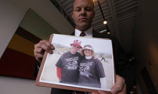 Attorney Paxton Guymon holds a photograph of Jim and Jan Harding following a news conference Thursday, Aug. 21, 2014, in Salt Lake City. Jan Harding, 67, drank sweet tea containing a toxic cleaning chemical, severely burning her mouth and throat at a Utah restaurant after an employee mistook the substance for sugar and mixed it into a dispenser. Harding is listed in good condition at a Salt Lake City hospital as she continues to improve. Authorities say a worker at Dickey's Barbecue in South Jordan unintentionally put the chemical cleaning compound in a sugar bag last month.  (AP Photo/Rick Bowmer)