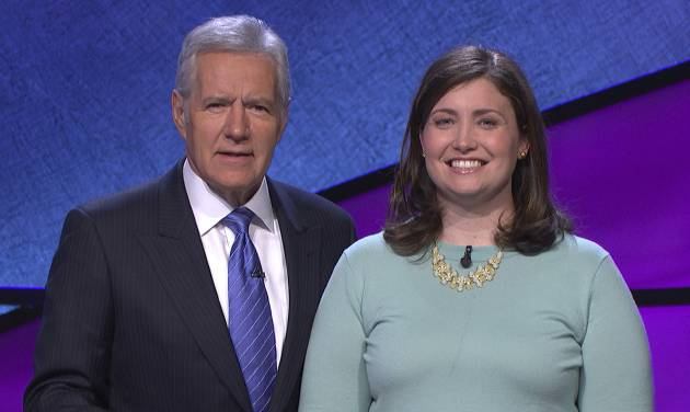 """In this January 2014 photo provided by Jeopardy Productions, Inc., shows Alex Trebek, host of the TV show """"Jeopardy!,"""" poses with contestant Julia Collins, 31, of Kenilworth, Ill., during the taping of her shows on stage at JEOPARDY!, Sony Pictures Studios, Culver City, Calif. On a show that aired Tuesday, May 27, 2014, Collins won her 17th straight game on Jeopardy! and has won more games than all but two other contestants in the history of the show. (AP Photo/Courtesy of Jeopardy Productions, Inc.)"""