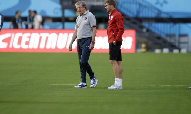 England's manager Roy Hodgson, left, and captain Steven Gerrard look at the quality of the pitch at the start of a training session of the England national soccer team at the Arena da Amazonia in Manaus, Brazil, Friday, June 13, 2014.  England play Italy in group D of the 2014 soccer World Cup at the stadium on Saturday.  (AP Photo/Matt Dunham)