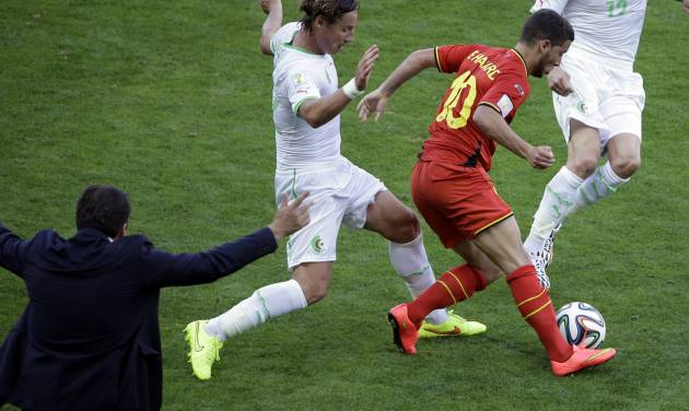 Belgium's Eden Hazard controls the ball past Algeria's Mehdi Mostefa as Belgium's head coach Marc Wilmots gestures on the sidelines during the group H World Cup soccer match between Belgium and Algeria at the Mineirao Stadium in Belo Horizonte, Brazil, Tuesday, June 17, 2014. (AP Photo/Sergei Grits)