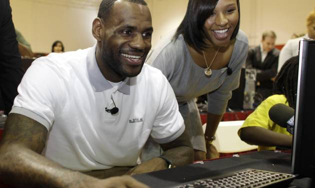 FILE - In a March 2, 2011 file photo, Miami Heat basketball player LeBron James, center, sits with his girlfriend Savannah Brinson, right, at a new computer during a charity event at the Northwest Boys & Girls Club in Miami. James married Savannah Brinson at the posh Grand Del Mar Hotel in San Diego on Saturday, Sept. 15, 2013, according to two people familiar with the details of the ceremony. About 200 guests were present for the ceremony, said one of the people, both of whom spoke on condition of anonymity because the wedding was private and the couple had yet to release any details. James and Brinson, 27, have been together since high school and have two sons. (AP Photo/Lynne Sladky, File)