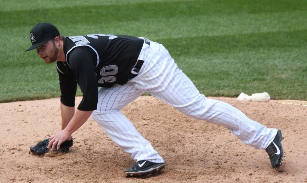 Colorado Rockies starting pitcher Brett Anderson loses his footing while delivering a pitch to Minnesota Twins' Phil Hughes in the fifth inning of an interleague baseball game in Denver on Sunday, July 13, 2014. (AP Photo/David Zalubowski)