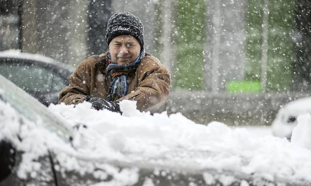 Curt Anderson clears snow off his vechicle in downtown Austin, Minn., Thursday, Feb. 20, 2014 as the winter storm covering the area moves through. (AP/Austin Daily Herald, Eric Johnson)