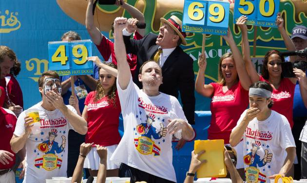 Joey Chestnut, center, wins the Nathan's Famous Fourth of July International Hot Dog Eating contest with a total of 69 hot dogs and buns, alongside Tim Janus, left, and Matt Stonie, right, Thursday, July 4, 2013 at Coney Island, in the Brooklyn borough of New York. (AP Photo/John Minchillo)