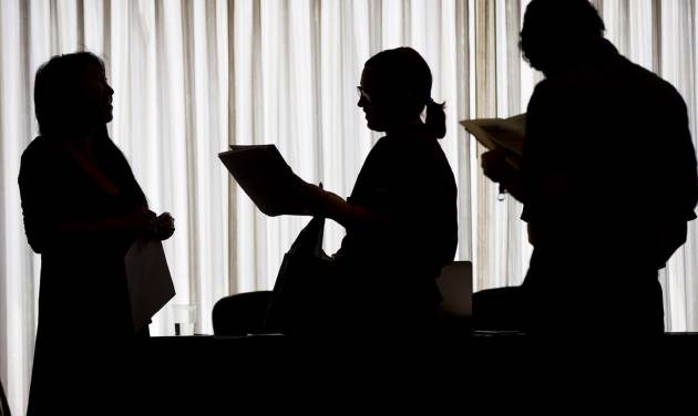 In this June 23, 2014 photo, recruiter Christina O, left, with New Western Acquisitions, meets with employment seekers during a job fair in Philadelphia. As the economic recovery enters its sixth year, many Americans don't feel better off. (AP Photo/Matt Rourke)