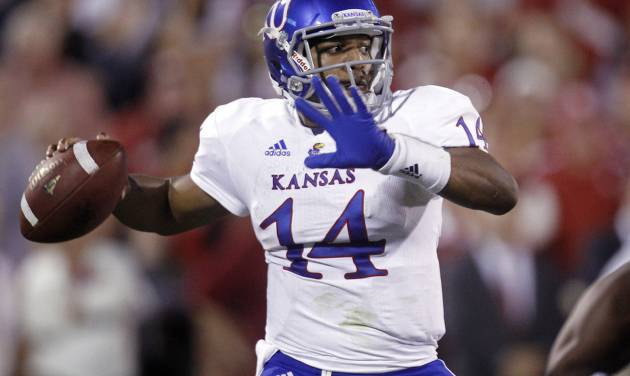 FILE - In this Oct. 20, 2012, file photo Kansas quarterback Michael Cummings throws a pass against Oklahoma in the fourth quarter of an NCAA college football game in Norman, Okla. Weis is sticking with his young quarterback when Kansas plays Texas on Saturday. (AP Photo/Sue Ogrocki, File)