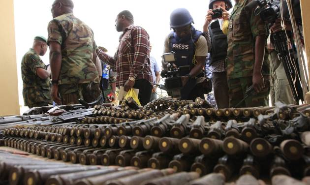 FILE In this Wednesday, June 5, 2013 file photo, journalists look at arms and ammunition which military commanders say they seized from Islamic fighters, in Maiduguri, Nigeria, on Wednesday, June 5, 2013. Boko Haram, the radical group that once attacked only government institutions and security forces, is increasingly targeting civilians. Some 155,000 square kilometers (60,000 square miles) of Nigeria are now under a state of emergency. On Friday, June 21, 2013, villagers streamed into Maiduguri from the Gwoza hills, saying Boko Haram fighters were threatening a bloodbath in the area where they appear to have regrouped, scrubby mountains with rock caves some 150 kilometers (90 miles) from the city. (AP Photo/Jon Gambrell, File)