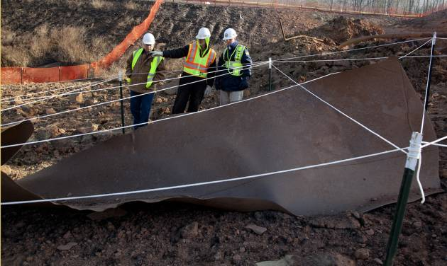This image provided by the National Transportation Safety Board Wednesday Dec. 12, 2012 shows investigators looking over a 20-foot-long section of pipe  found more than 40 feet from the rupture site in Sissonville, W.V.  The 20-inch transmission pipe exploded around midday Tuesday, destroying four homes, cooking a section of Interstate 77, a major north-south commuting corridor that passes through the capital city, and creating a crater 17 feet deep. (AP Photo/NTSB)