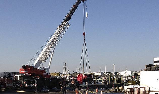A crane lifts a car from the water in Newport, R.I., Friday, Oct. 5, 2012. The bodies of three women were pulled Friday from the car, that had been in Newport Harbor for hours after it plunged off a pier and landed on its roof, police said. (AP Photo/Newport Daily News, Matt Sheley)
