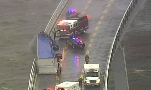 In this image from video provided by WJZ-TV, emergency crews surround a tractor-trailer that overturned on the westbound span of the Bay Bridge, which crosses the Chesapeake Bay in Maryland. The bridge was closed in both directions after the crash Wednesday afternoon due to high winds from a snowstorm blowing through the Mid-Atlantic region. (AP Photo/WJZ-TV)