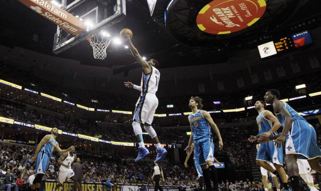 Memphis Grizzlies' Mike Conley (11) goes to the basket in front of New Orleans Hornets' Robin Lopez (15) during the first half of an NBA basketball game in Memphis, Tenn., Saturday, March 9, 2013. (AP Photo/Danny Johnston)