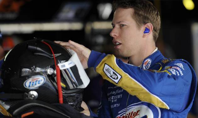 Driver Brad Keselowski prepares his helmet before practice for the AAA 400 NASCAR Sprint Cup Series auto race, Friday, Sept. 28, 2012, in Dover, Del. (AP Photo/Nick Wass)