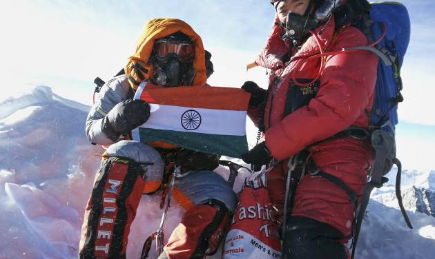 In this Sunday, May 25, 2014 handout photo, Malavath Poorna, left, holds up her nation's flag on Mount Everest, Nepal. A social charity says the 13-year-old daughter of poor Indian farmers has become the youngest girl to climb Mount Everest. Poorna says she and a team of Nepalese climbing guides made it to the top on May 25 from the northern side in Tibet. (AP Photo/Andhra Pradesh Information Center)