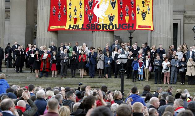 People gather at St George's Place to attend a vigil in memory of the 96 victims of the Hillsborough stadium disaster in Liverpool, England, Sept. 12, 2012. British police and medics whose failures contributed to the deaths of 96 soccer fans in the country's worst sports disaster unfairly blamed the dead for the 1989 tragedy and sought to cover up their actions, newly disclosed documents revealed Wednesday. (AP Photo/PA, Peter Byrne) UNITED KINGDOM OUT, NO SALES, NO ARCHIVE
