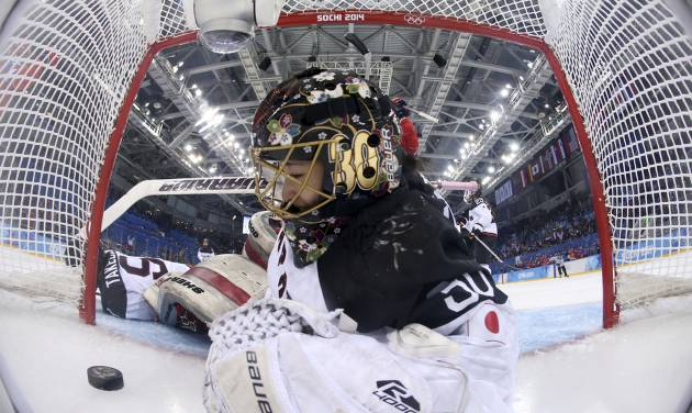 Goalkeeper Nana Fujimoto of Japan looks at the puck after sliding in after it on a score by Galina Skiba of Russia during the 2014 Winter Olympics women's ice hockey game at Shayba Arena, Sunday, Feb. 16, 2014, in Sochi, Russia. Russia defeated Japan 6-3. (AP Photo/Martin Rose, Pool)
