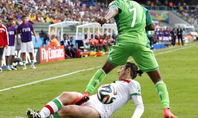 Iran's Andranik Teymourian slides under Nigeria's Ahmed Musa to take the ball away during the group F World Cup soccer match between Iran and Nigeria at the Arena da Baixada in Curitiba, Brazil, Monday, June 16, 2014.  (AP Photo/Jon Super)
