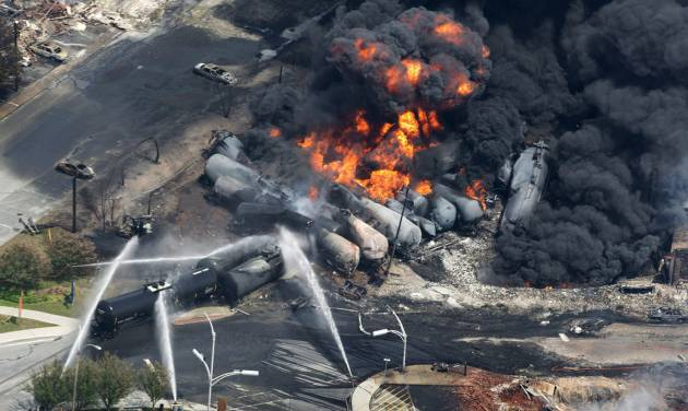 In this Saturday, July 6, 2013 photo, smoke rises from railway cars carrying crude oil after derailing in downtown Lac Megantic, Quebec. Lac-Megantic still struggles to recover as it marks the disaster's one-year anniversary. (AP Photo/The Canadian Press, Paul Chiasson)